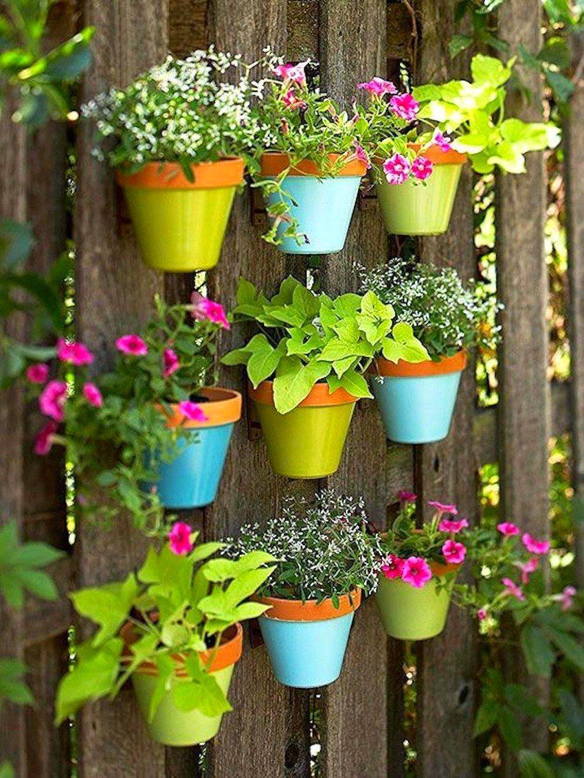Вертикальная клумба из разноцветных горшков украшает деревянную изгородь.